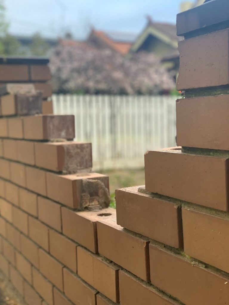 """""""Photo of a brick fence needing brick repairs in Toowoomba - Bricklayers in Toowoomba performing repairs on a brick fence - Damaged brick fence that requires repair work in Toowoomba """""""